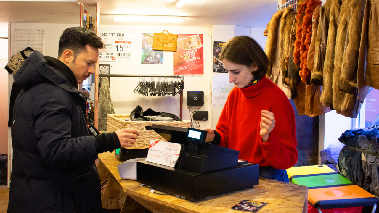 Sales assistent sells a item in a vintage shop infront of used coats out of fur.
